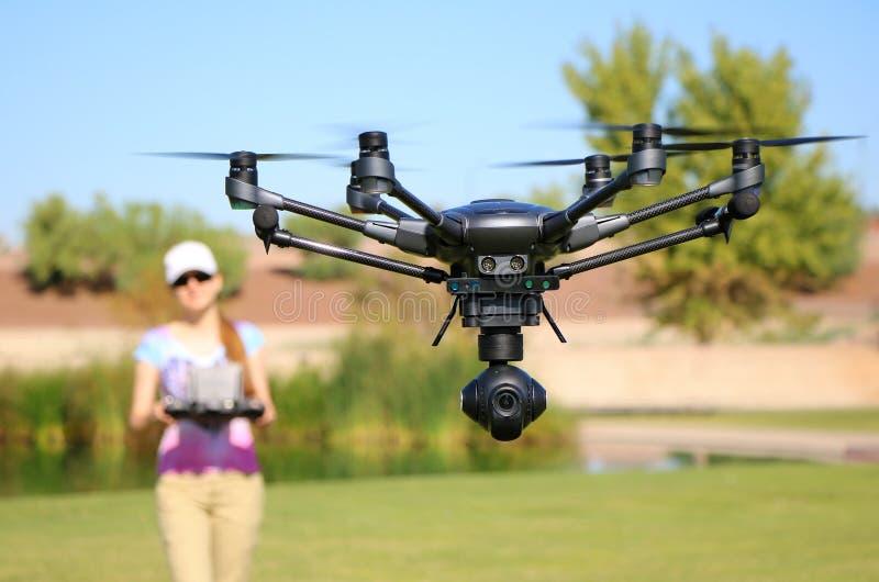 Kvinna som flyger ett tekniskt avancerat kamerasurr royaltyfria bilder