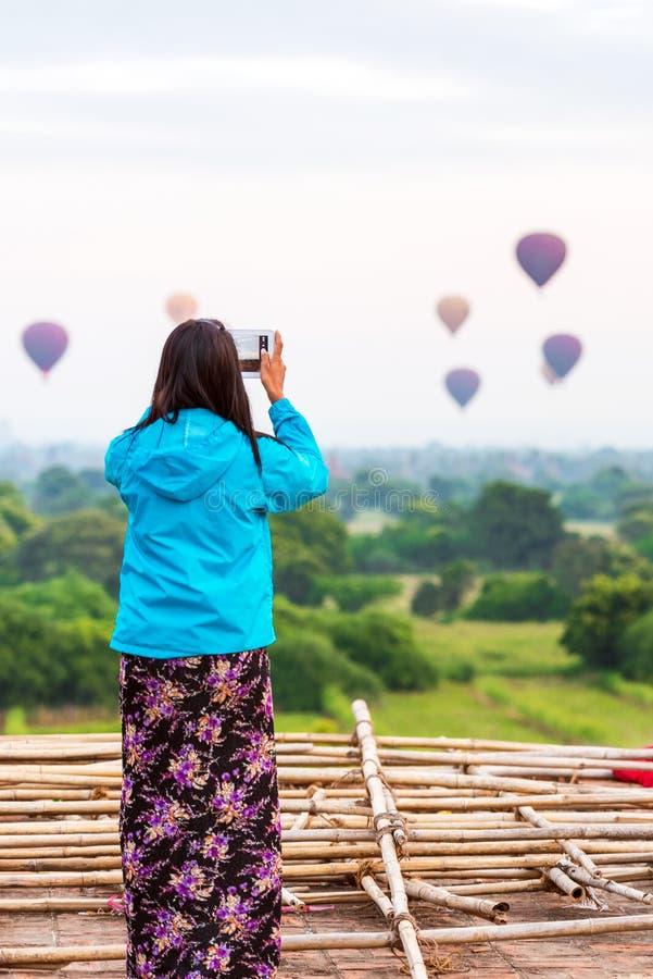 Kvinna som fotograferar ballonger i Bagan, Myanmar Kopiera utrymme för text tillbaka sikt vertikalt royaltyfri bild