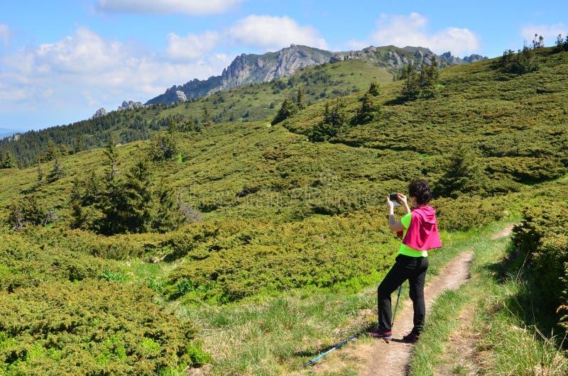 Kvinna som fotograferar berg royaltyfri bild