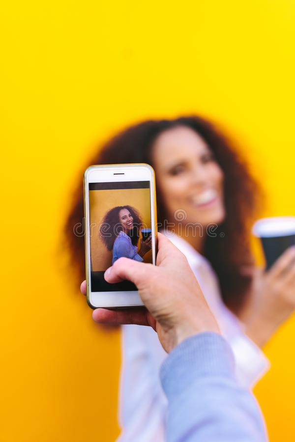 Kvinna som fotograferar vännen med mobiltelefonen arkivfoto
