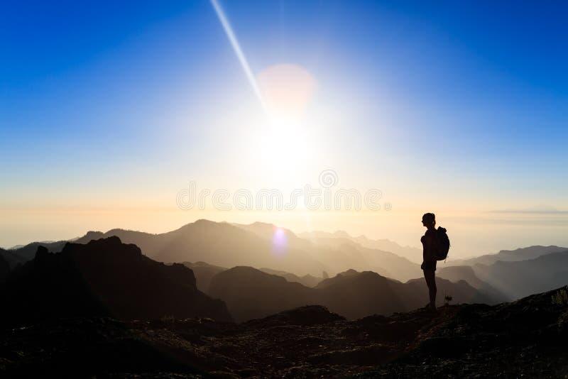 Kvinna som fotvandrar framgångkonturn i bergsolnedgång fotografering för bildbyråer
