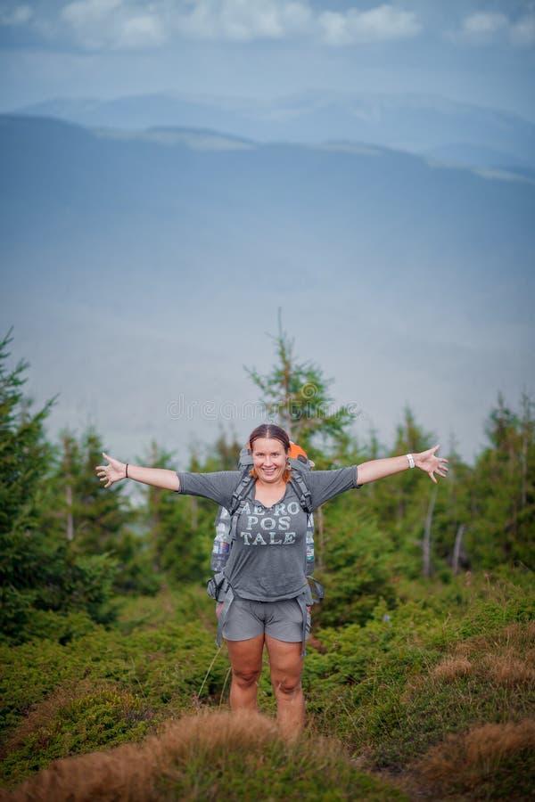 Kvinna som fotvandrar i höstskog i berg royaltyfri foto