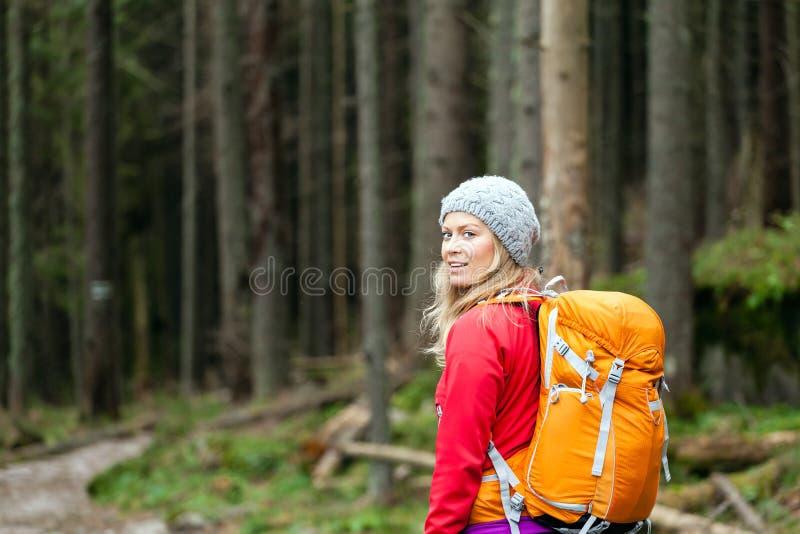 Kvinna som fotvandrar i skog royaltyfri bild
