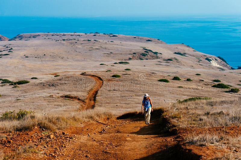 Kvinna som fotvandrar på ön med havet i bakgrund arkivbild