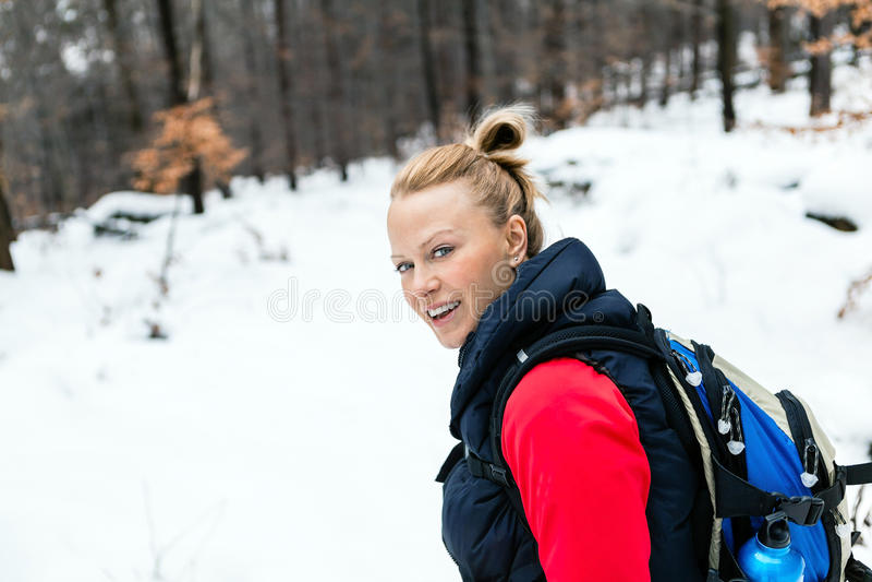 Kvinna som fotvandrar på insnöad vinterskog royaltyfria foton