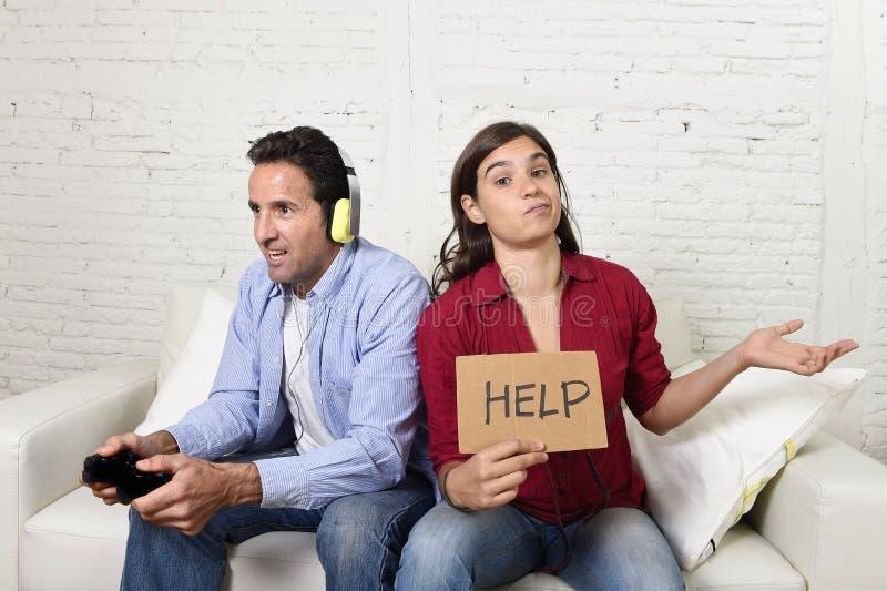 Kvinna som frågar för ilsken rubbning för hjälp, medan maken eller pojkvännen spelar videogames som ignorerar henne royaltyfria bilder