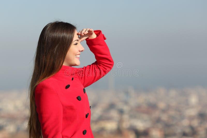 Kvinna som framåtriktat ser med staden i bakgrunden arkivbilder