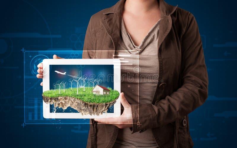 Kvinna som framlägger ett perfekt ekologiland med ett hus och en windmil arkivbilder