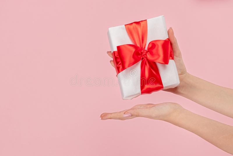 Kvinna som framlägger gåvaasken med den röda pilbågen fotografering för bildbyråer