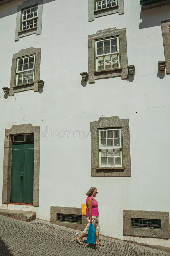 Kvinna som framme går ner gränden av huset royaltyfria foton