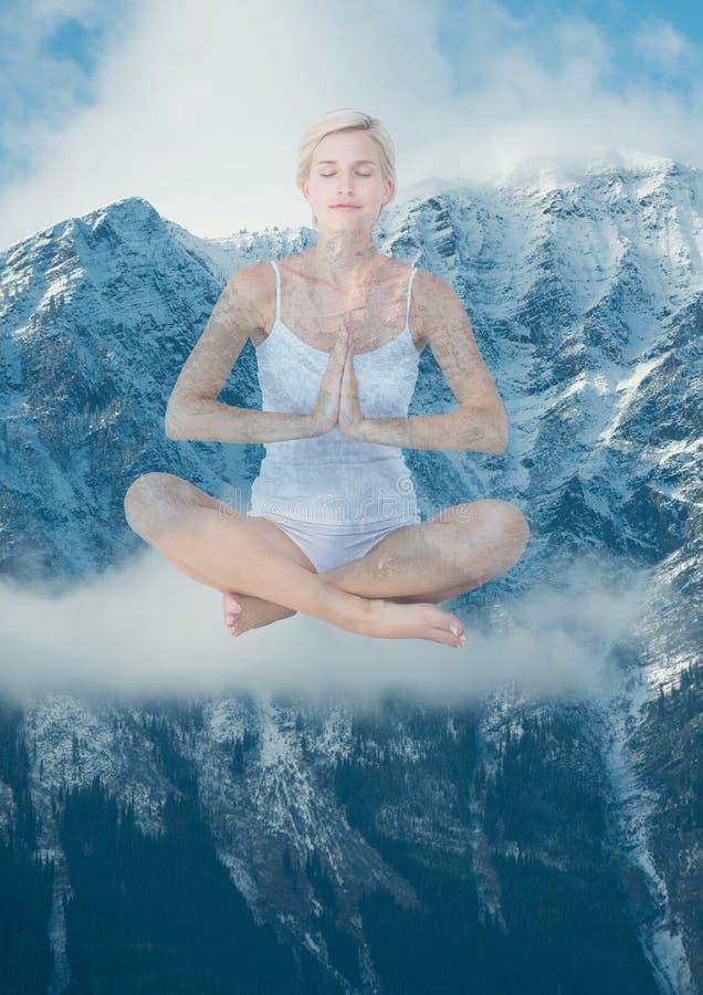 Kvinna som framme gör yoga av snö-täckte berg royaltyfri fotografi