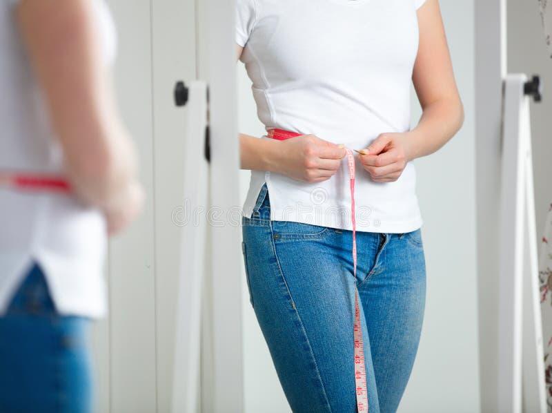 Kvinna som framme mäter midjan av spegeln royaltyfri bild