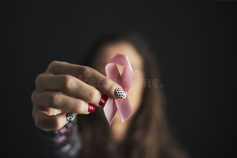 Kvinna som framme rymmer ett rosa band av hennes framsida royaltyfri bild