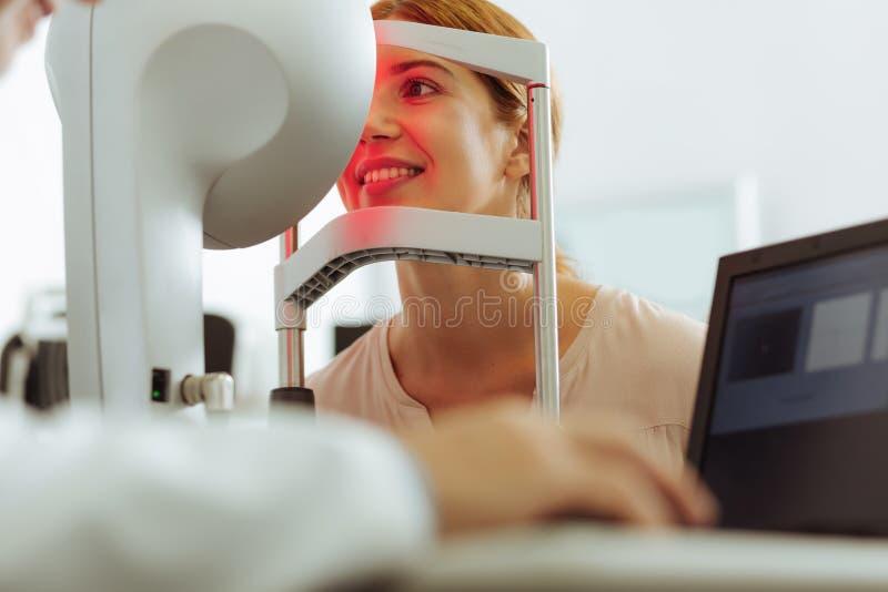 Kvinna som framme sitter av ögondoktor, medan komma för konsultation arkivfoto