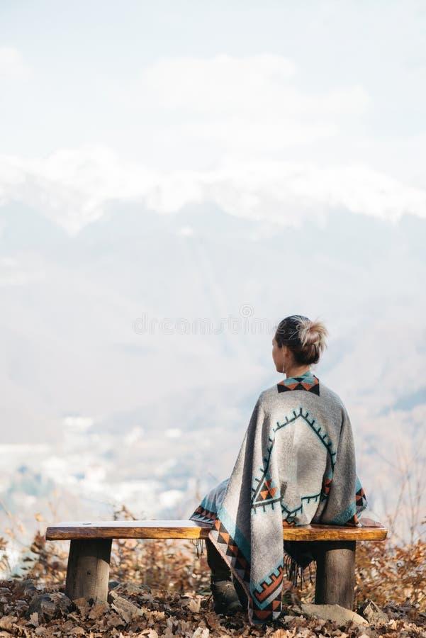 Kvinna som framme vilar på en bänk av berg arkivbild
