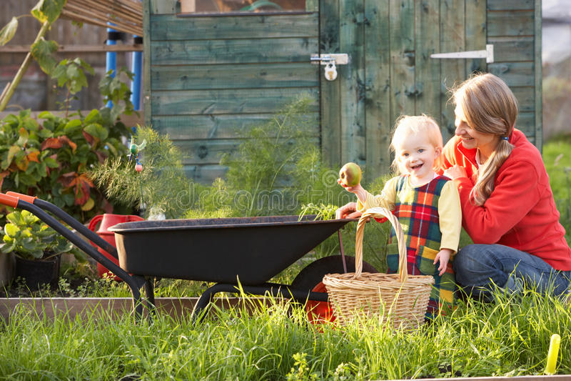 Kvinna som fungerar på odlingslott med barnet royaltyfri bild