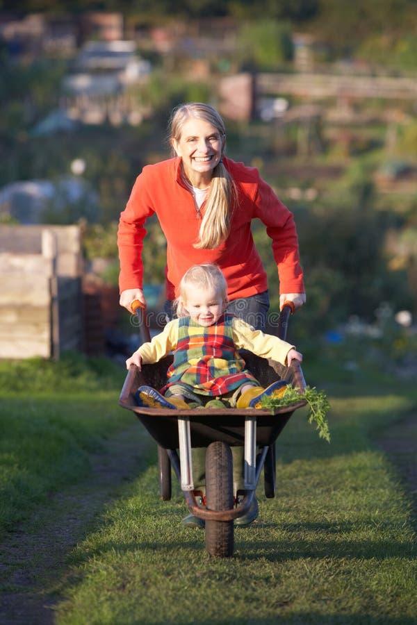 Kvinna som fungerar på odlingslott med barnet royaltyfri fotografi