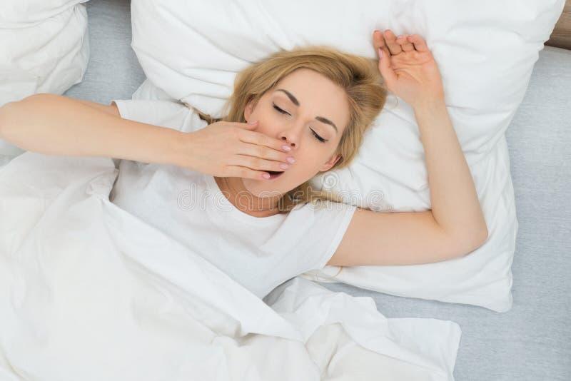 Kvinna som gäspar i sovrum royaltyfri foto