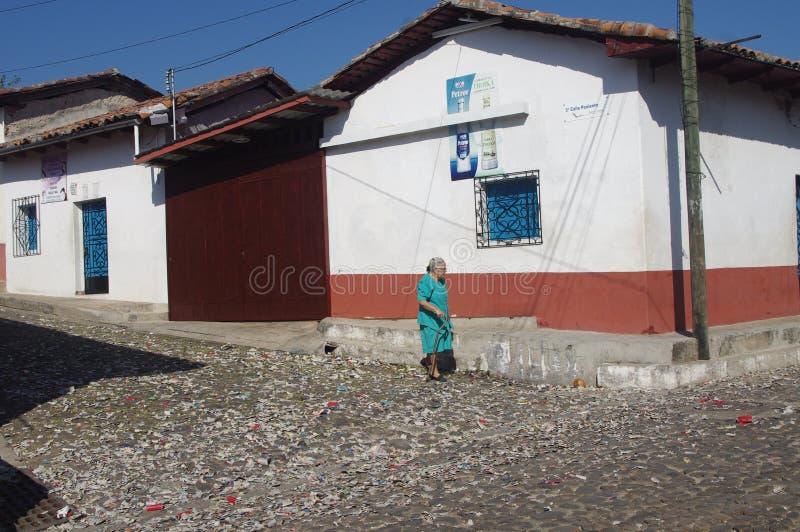 Kvinna som går den tysta gatan i Suchitoto royaltyfria bilder