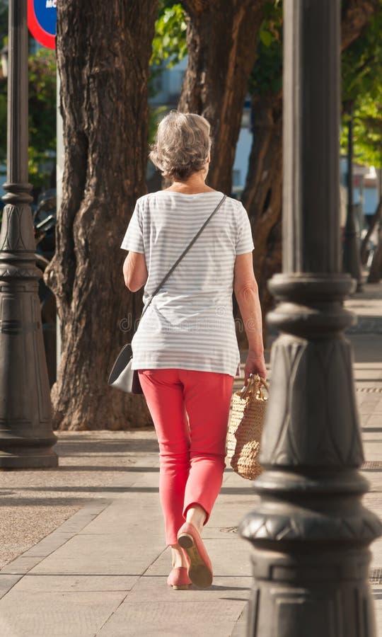 Kvinna som går en trottoar med handväskan i Cadiz, Spanien arkivfoto