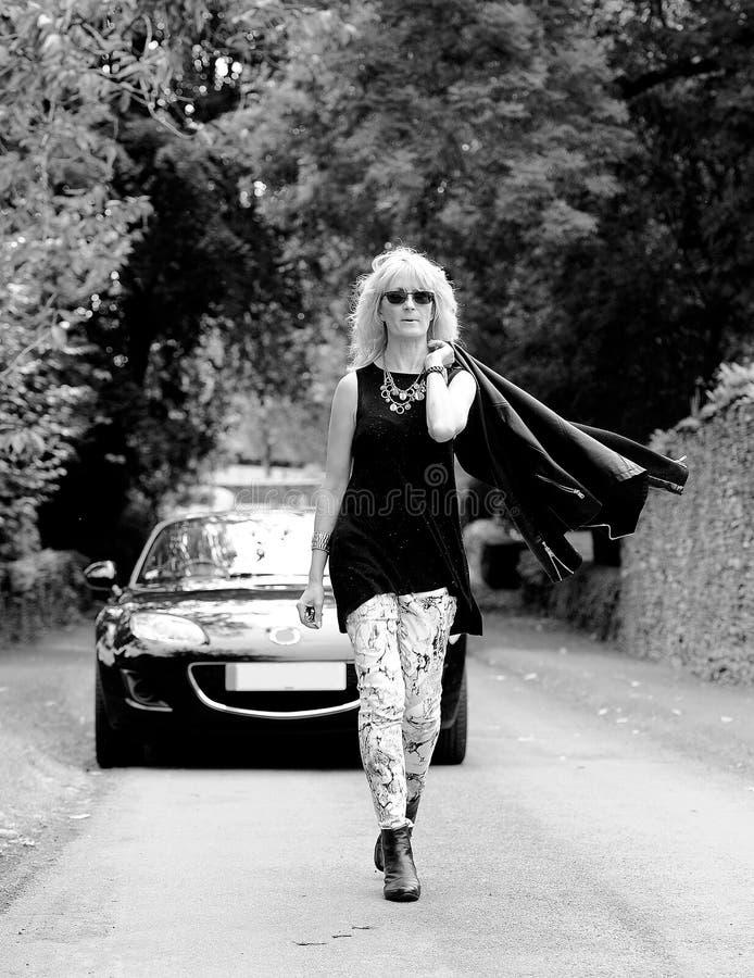 Kvinna som går framåt av sportbilen B&W arkivfoton
