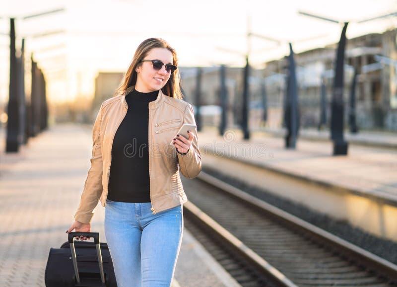 Kvinna som går i drevstation och använder smartphonen royaltyfria bilder