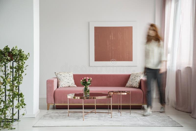 Kvinna som går i en kvinnlig vardagsruminre med en soffa, en kaffetabell och måla royaltyfria bilder