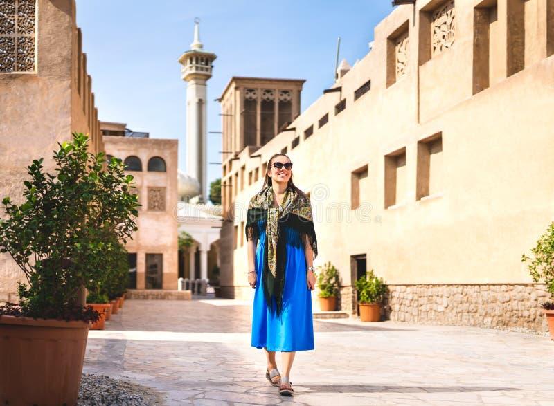 Kvinna som går i gamla Dubai, UAE Traditionell arabisk gata och moské Kvinnlig turist i den historiska Al Fahidi neighbourhooden arkivfoto