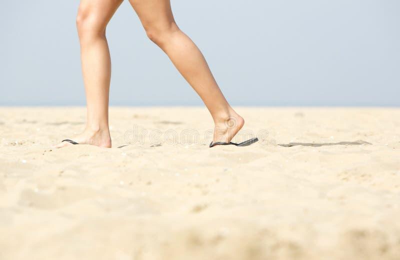 Kvinna som går i sandaler på sand royaltyfria bilder