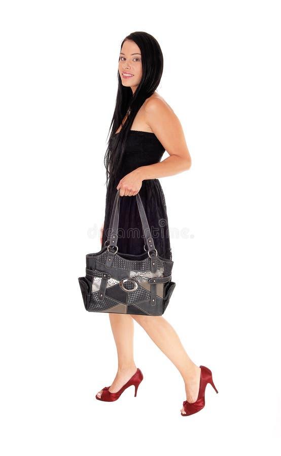 Kvinna som går i svart klänning och handväska royaltyfri foto