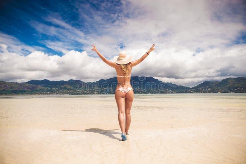Kvinna som går med händer i luften på stranden royaltyfria bilder