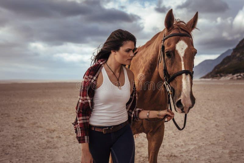 Kvinna som går med hästen på kusten royaltyfri foto