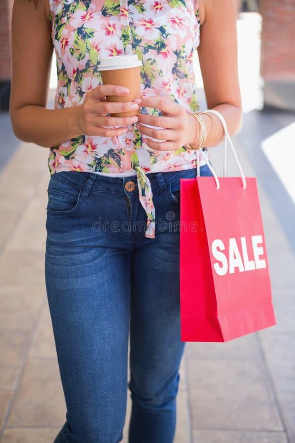 Kvinna som går med kaffe för att gå och shoppingpåsen royaltyfri foto