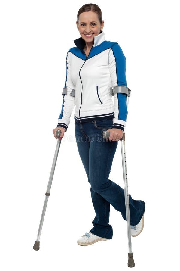 Kvinna som går med servicen av kryckor royaltyfria bilder