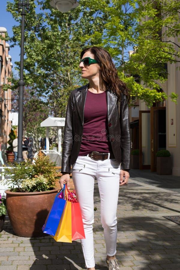 Kvinna som går med shoppingpåsar på gatan arkivbilder