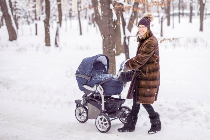 Kvinna som går med sittvagnen i skog på vintern royaltyfri bild