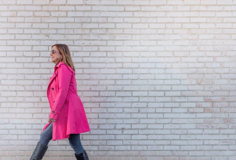 Kvinna som går mot tegelstenväggen - som överexponeras för effekt royaltyfri bild
