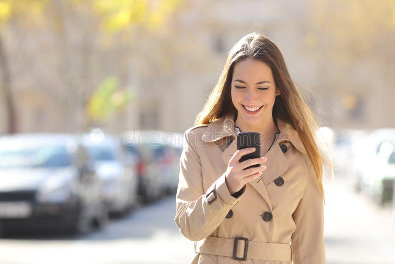 Kvinna som går och använder en smart telefon på gatan arkivfoto