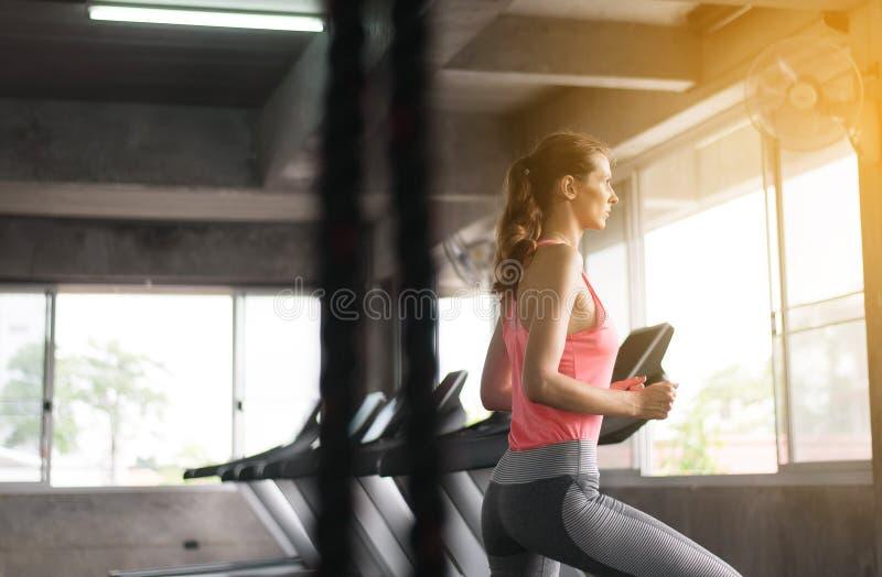 Kvinna som går och kör cardio utbildning i en idrottshall, sunt livsstilbegrepp arkivbild