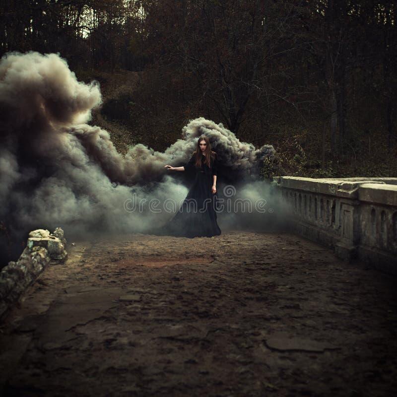 Kvinna som går på bron i skurkrollsvartrök royaltyfria foton