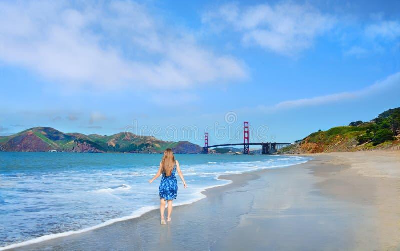 Kvinna som går på den härliga stranden på sommarsemester arkivfoto