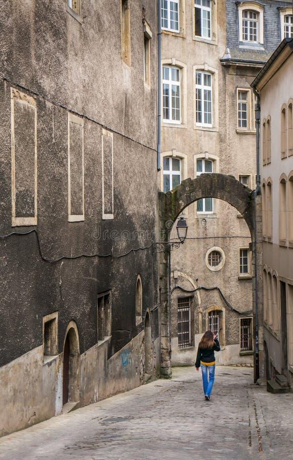 Kvinna som går på en medeltida gata i Luxembourg royaltyfri foto