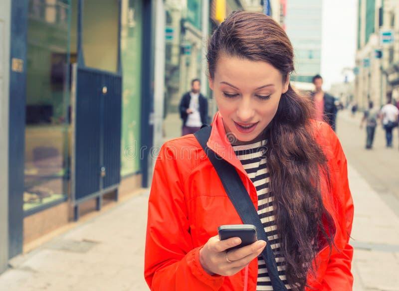 Kvinna som går på en stadsgata och använder hennes mobiltelefon arkivfoto