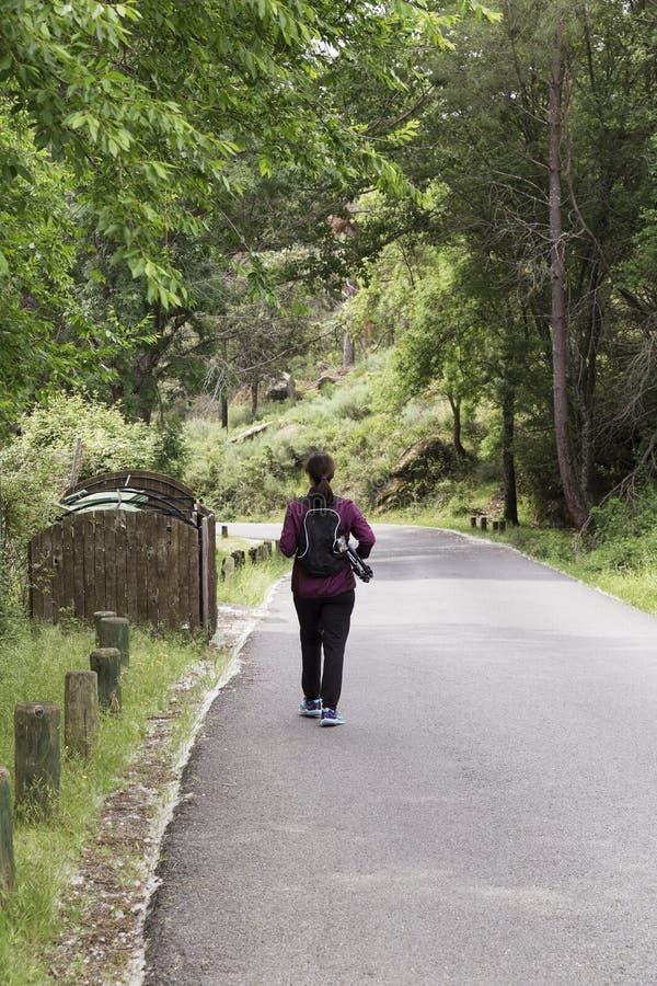 Kvinna som går på en väg arkivbilder