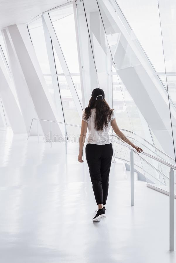 Kvinna som går på ett modernt hall arkivbild