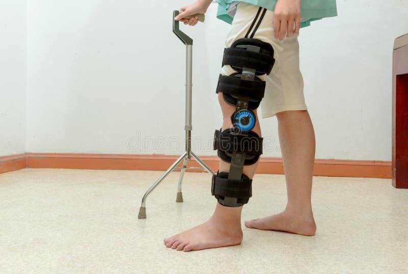 Kvinna som går på kryckor, bärande knäservice royaltyfri foto