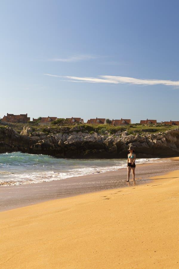 Kvinna som går på sanden av en härlig strand royaltyfria bilder