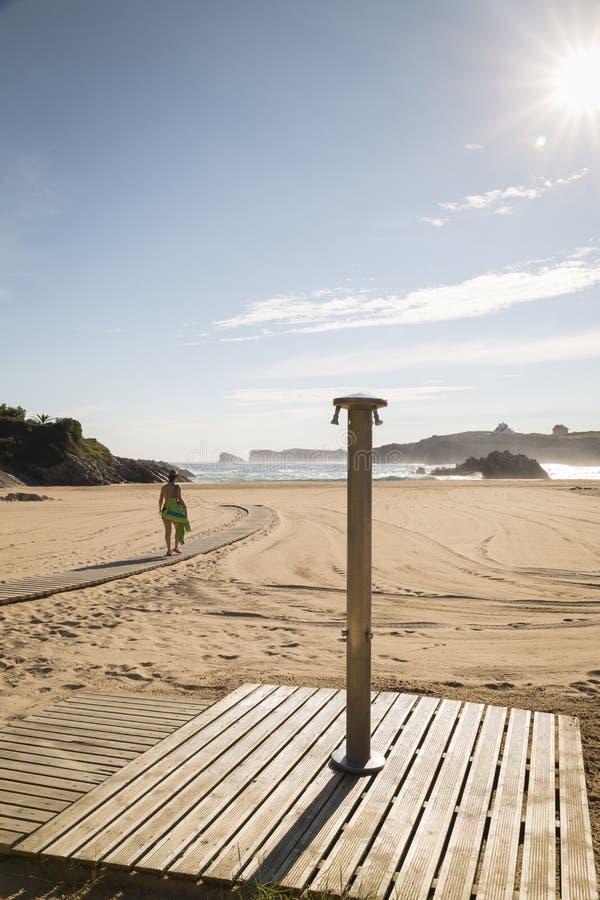 Kvinna som går på sanden av en härlig strand arkivfoto