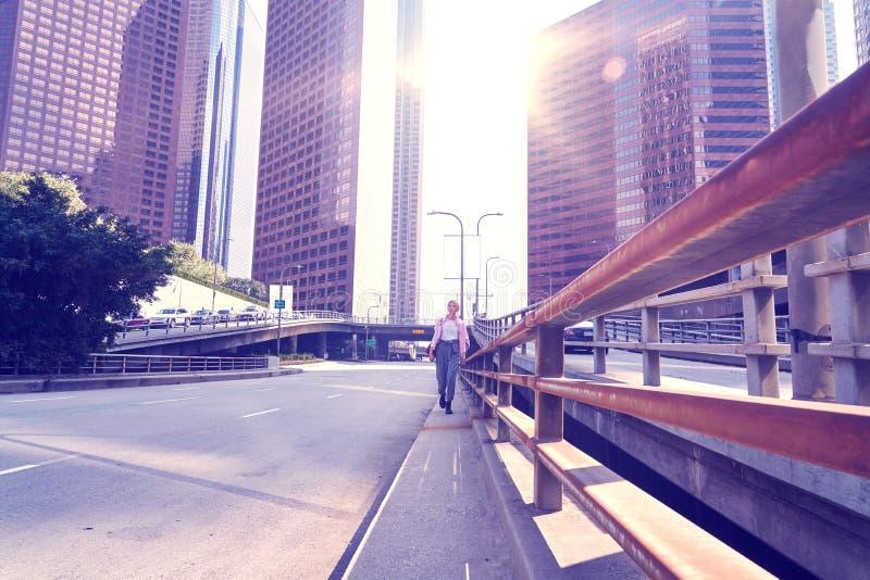 Kvinna som går på stadsvägen vid skyskrapabyggnads- och himmelsikten, finansiellt område arkivbild