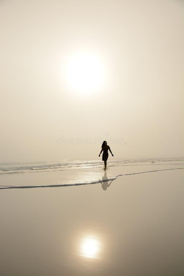 Kvinna som går på stranden fotografering för bildbyråer